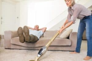 man-resting-on-couch-while-woman-vacuuming-area-rug.jpg